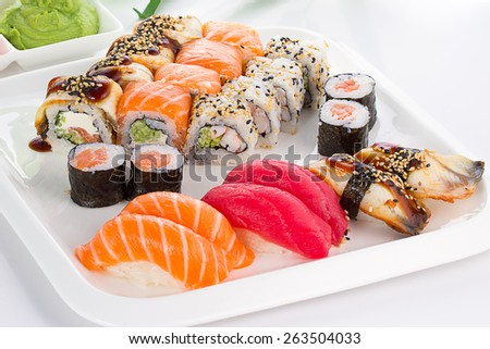 Sushi set on white plate over white background - stock photo