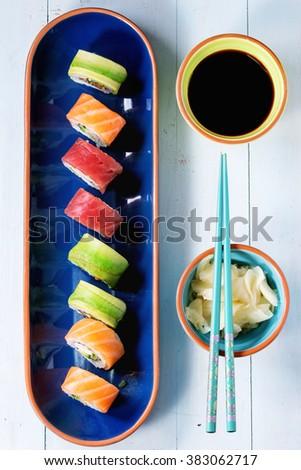 Sushi set salmon and avocado rolls served in bright ceramic plates with chopsticks and soy sauce on blue wooden table. Flat lay - stock photo