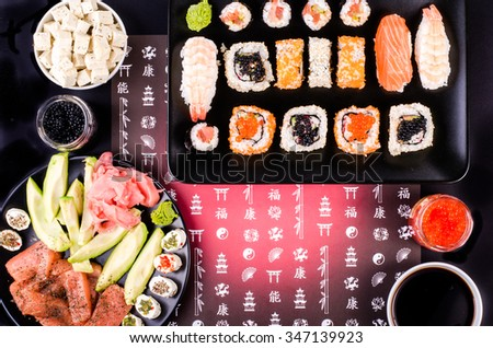 Sushi set, soy sauce, ginger, wasabi, black and red roe, avocado, salmon, cheese on black background with Japanese characters - stock photo