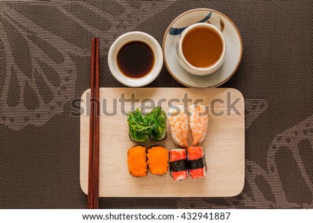 Sushi set with chop sticks and soy sauce served on wooden slate - Sushi is a food originating in Japan, consisting of cooked vinegar rice combined with other ingredients such as seafood, vegetables - stock photo