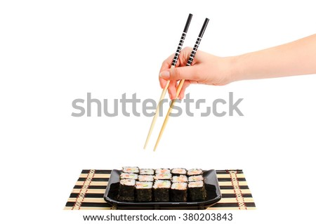 Sushi set with red fish, a cucumber and shrimps on a black plate. The female hand takes sushi. The girl's hand on a white background with Japanese chopsticks. - stock photo