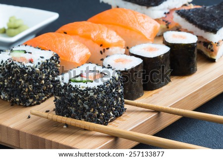 Sushi with chopsticks, selective focus at front - stock photo