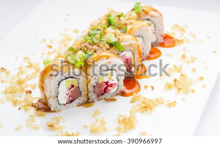 Sushi with shrimp avocado salmon and cheese strewed with green onion. Crunch Roll. With delicious sauces. On a plate over white background. - stock photo