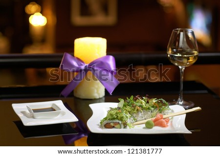 sushi with white wine on a table at restaurant - stock photo