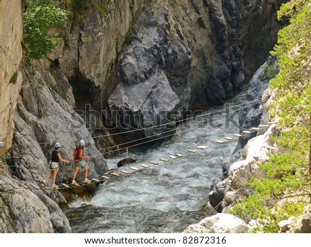suspensed bridge over wild water - stock photo