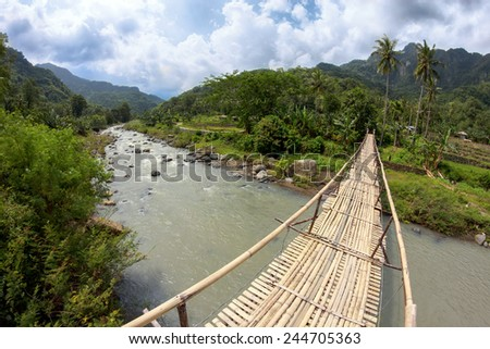 Suspension bamboo bridge across the river in a forest and rice field - stock photo