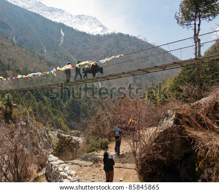 Suspension bridge across the river on the trail to Everest - Nepal - stock photo