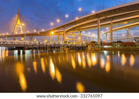 Suspension bridge and highway curved riverside with twilight scene - stock photo
