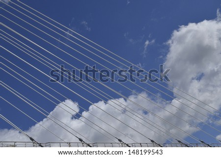 Suspension bridge cables shown against blue sky with white clouds - stock photo