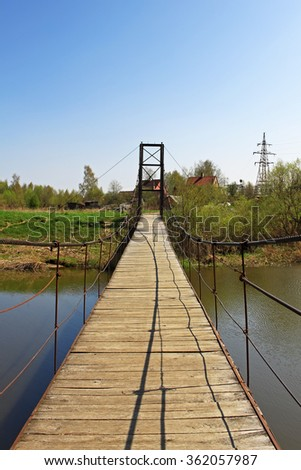 Suspension bridge over the river near the hydroelectric power plant - stock photo