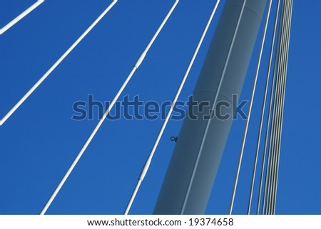 suspension bridge tension cable abstract against a blue sky - stock photo