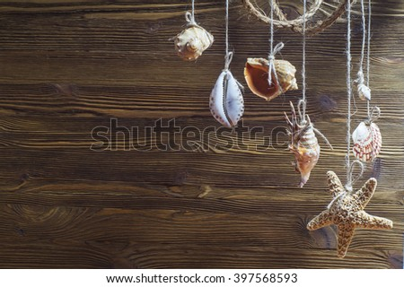 Suspension of sea shells and sea stars on wooden background. Seashells and starfish hanging on the rope, vintage styling - stock photo