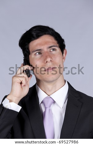 Suspicious Businessman talking on his cellular (isolated on gray) - stock photo