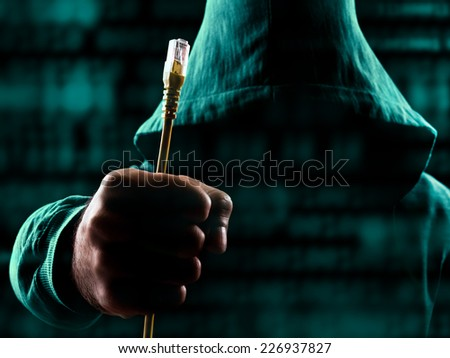 Suspicious man with hood holding unplugged internet cable surrounded with data - stock photo