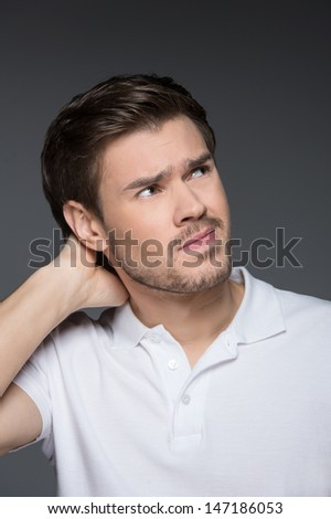 Suspicious men. Portrait of worried young men holding his hand in hair while isolated on grey - stock photo