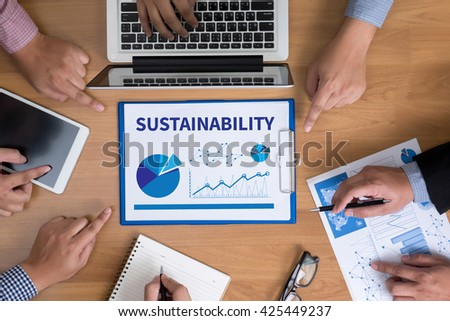 SUSTAINABILITY Business team hands at work with financial reports and a laptop, top view - stock photo