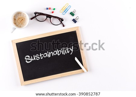 Sustainability word on chalkboard with coffee cup and eyeglasses, view from above - stock photo