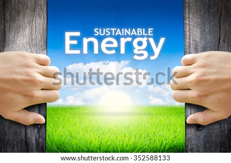 """Sustainable energy. Hand opening an old wooden door and found wording """"Sustainable energy"""" over green field and bright blue Sky Sunrise. - stock photo"""