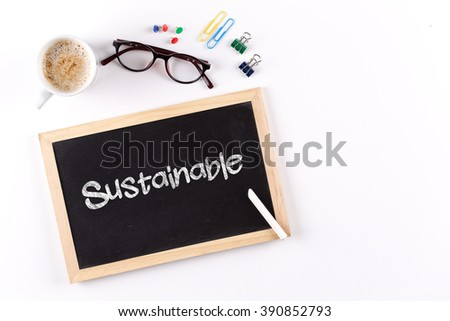 Sustainable word on chalkboard with coffee cup and eyeglasses, view from above - stock photo