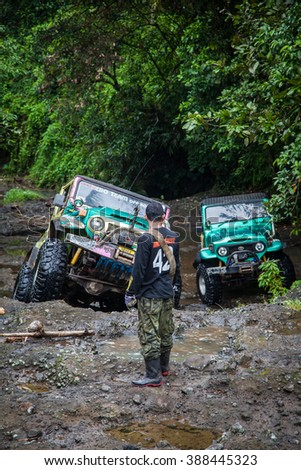 SUV in the tropical jungle - March 7, 2013 Indonesia, Bali.  Adventure car enthusiast wading a rocky river  using modified four wheel car in the jungle. - stock photo