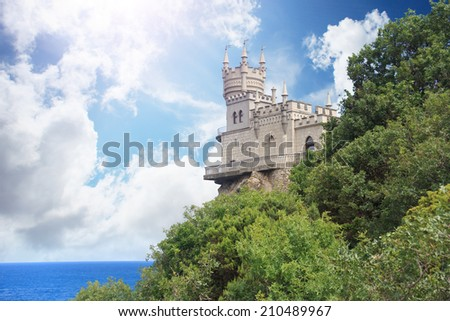 Swallow's Nest Castle in park with clouds sky and dark sea - stock photo