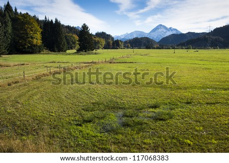 swamp and meadow at autumn with sky, clouds and mountains - stock photo