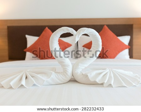 swans made from towels on the bed. - stock photo