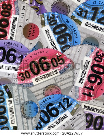 SWANSEA, UK - JULY 11, 2014: Photo of a collection of UK car tax discs showing different years. - stock photo