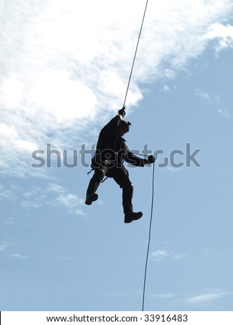 SWAT team member rappelling at counter terrorism training - stock photo