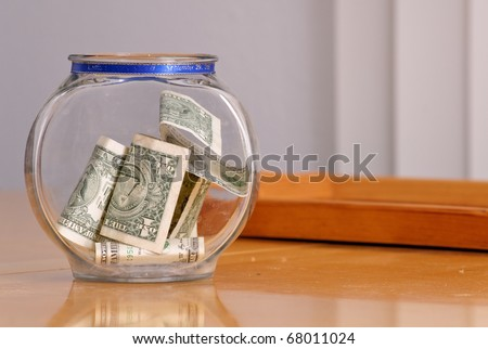 Swear Jar with Money on Table - stock photo