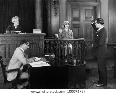 Swearing in witness in courtroom - stock photo
