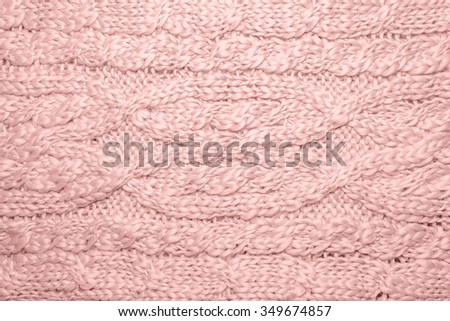 Sweater or scarf texture. Knitted jersey background with a relief pattern. Braids in knitting. Wool hand-knitted or machine knitting pattern. Rose quartz fashion and home color on Fabric Background.  - stock photo