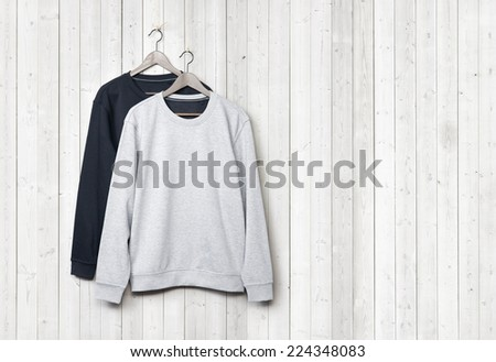 Sweaters on a white wood wall - stock photo