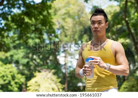 Sweaty man drinking after running - stock photo