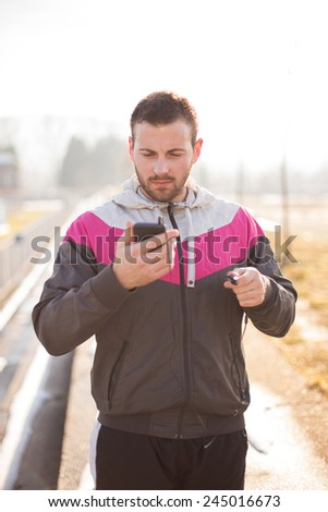 Sweaty Man is perparing for a run outside. He is looking at his smartphone. He is wearing earbud.  - stock photo