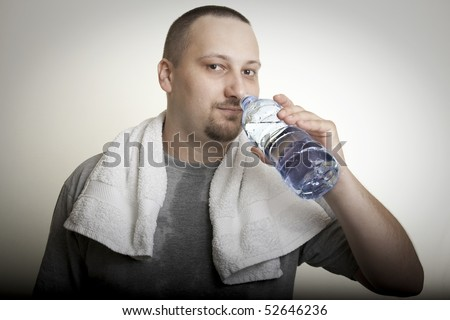 sweaty man with a white towel around his neck, drinking water after exercise - stock photo
