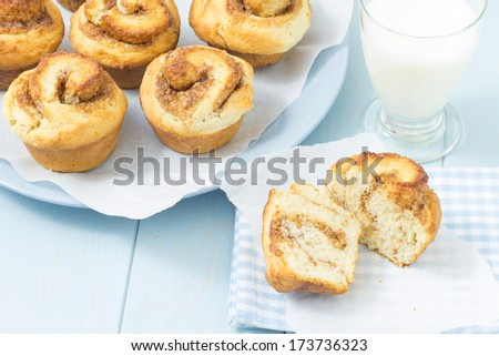 Swedish cinnamon buns on plates with a glass of milk - stock photo
