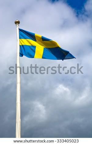 Swedish flag against storm gray skies in sunshine, Sweden.  - stock photo