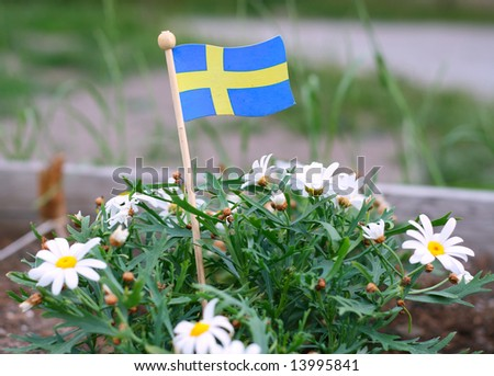 Swedish flag among the green plants - stock photo