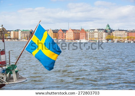 Swedish flag on the rear of a boat in Stockholm, with some colorful houses on the water edge on background. - stock photo
