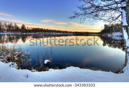 Swedish lake sunset in firs winter season - stock photo