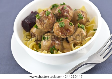 Swedish meatballs in creamy gravy with curly egg noodles and grape jelly - stock photo