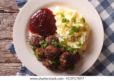 Swedish meatballs kottbullar, lingonberry sauce with a side dish mashed potato on the plate closeup. horizontal view from above - stock photo