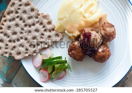 Swedish meatballs topped with lingonberry jam and served with mashed potato, crisp bread and salad. This popular Scandinavian dish is presented on a rustic wooden table. - stock photo
