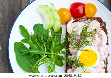 Swedish style rye bread open sandwich topped with prawns and boiled egg. Served on a rustic wooden table with a side salad of rocket leaves, tomato and cucumber and garnished with fresh dill. - stock photo