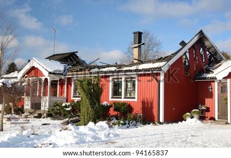 Swedish typical house burnt in winter season - stock photo