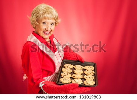Sweet adorable grandmother holding a pan of freshly baked chocolate chip cookies.   Photographed over red background with room for text. - stock photo