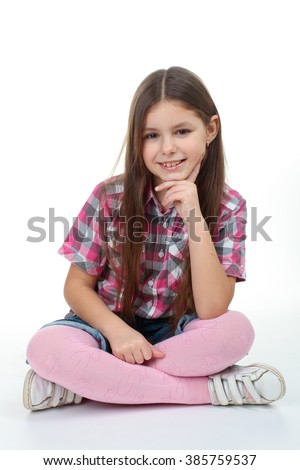 sweet and beautiful little girl sitting with crossed legs isolated on white background - stock photo