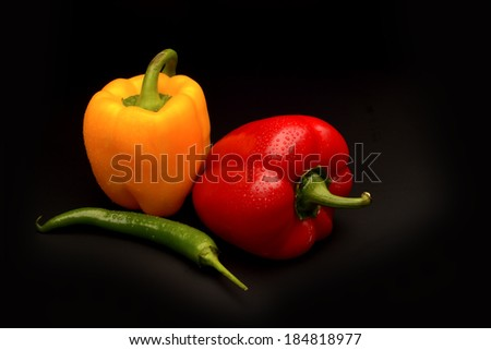 Sweet and chilli pepper on black background - stock photo