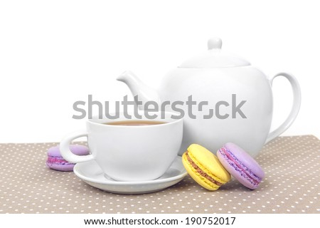 Sweet and colourful french macaroons with tea cup and teapot - stock photo